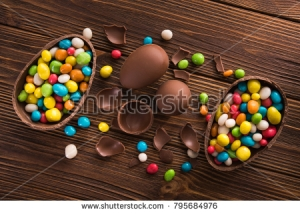 stock-photo-easter-dessert-tasty-chocolate-egg-with-color-candy-dragee-on-wooden-table-795684976